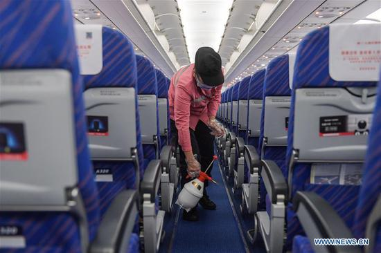 A staff member disinfects the cabin of an airplane after its arrival at the Haikou Meilan International Airport in Haikou, south China's Hainan Province, Jan. 31, 2020. China Southern Airlines has strengthened its efforts on the prevention and control of the novel coronavirus, demanding all the facilities inside the cabin to be disinfected after flight. (Photo by Pu Xiaoxu/Xinhua)