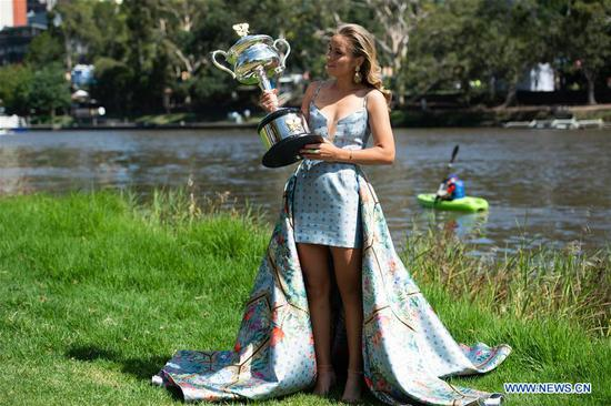 Australian Open women's singles champion Sofia Kenin of the United States poses for photographs with her trophy at Yarra River in Melbourne, Australia on Feb. 2, 2020. (Photo by Bai Xue/Xinhua)