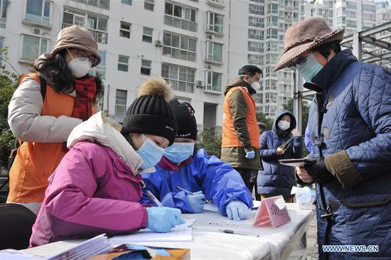 Staff members record residents' reservation information of masks inside a residential area of east China's Shanghai, Feb. 2, 2020. Various measures have been taken for epidemic prevention efforts across China. (Xinhua/Gao Feng)