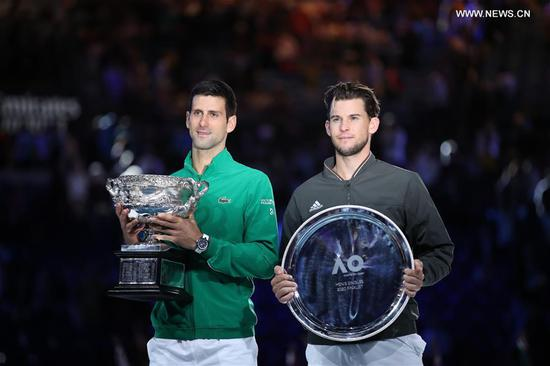 Novak Djokovic (L) of Serbia and Dominic Thiem of Austria pose for pictures during the awarding ceremony after the men's singles final at 2020 Australian Open in Melbourne, Australia on Feb. 2, 2020. (Xinhua/Bai Xuefei)