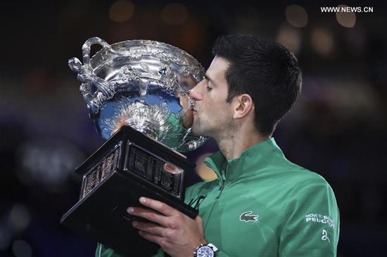 Novak Djokovic of Serbia kisses the trophy during the awarding ceremony after the men's singles final against Dominic Thiem of Austria at 2020 Australian Open in Melbourne, Australia on Feb. 2, 2020. (Xinhua/Bai Xuefei)