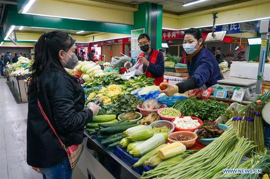Citizens buy vegetables at a market in Nanjing, east China's Jiangsu Province, Feb. 2, 2020. A total of 240 markets have resumed operation by noon on Sunday in Nanjing, so as to guarantee daily necessities supply. (Xinhua/Li Bo)