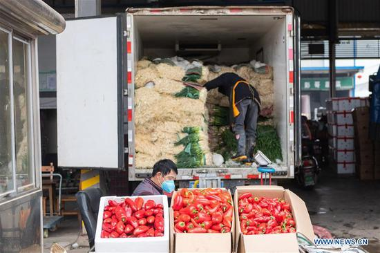 Vendors arrange vegetables at a logistics center of agricultural products in Changsha , central China's Hunan Province, Feb. 7, 2020. Changsha has been stepping up efforts to ensure continuous vegetable supply and stable prices in fighting against the novel coronavirus. (Photo by Chen Sihan/Xinhua)