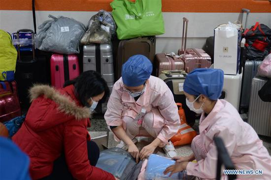 Medical team members of the Xiangya Hospital of Central South University arrange their luggages before setting out for Hubei Province in Changsha, central China's Hunan Province, Feb. 7, 2020. The third batch of medical teams comprised of 130 members from the Xiangya Hospital of Central South University set off on Friday to aid the coronavirus control efforts in Hubei. (Xinhua/Chen Zhenhai)
