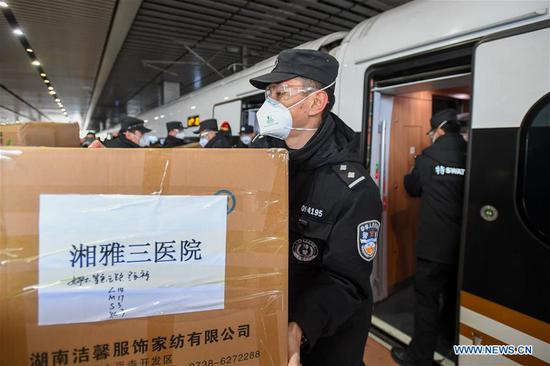 Staff members carry supplies for the medical team onto high speed trains at Changsha South Railway Station in Changshan, central China's Hunan Province, Feb. 8, 2020. Medical workers of the third batch from the Second Xiangya Hospital of Central South University and the first batch from the Third Xiangya Hospital of Central South University set off for Wuhan on Saturday, the Chinese Lantern Festival, to aid the novel coronavirus control efforts there. (Xinhua/Chen Zeguo)