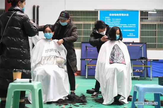 Medical team members have their hair cut to better wear protective products before leaving for Wuhan of Hubei Province, at the Third Xiangya Hospital of Central South University in Changsha, central China's Hunan Province, Feb. 8, 2020. Medical workers of the third batch from the Second Xiangya Hospital of Central South University and the first batch from the Third Xiangya Hospital of Central South University set off for Wuhan on Saturday, the Chinese Lantern Festival, to aid the novel coronavirus control efforts there. (Xinhua/Chen Zeguo)