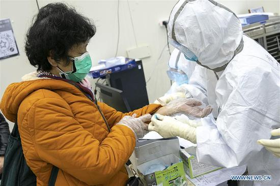 Medical staff ties a wrist band to a patient at a temporary hospital converted from