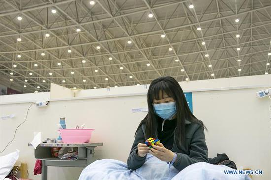 A patient solves a rubik's cube at a temporary hospital converted from