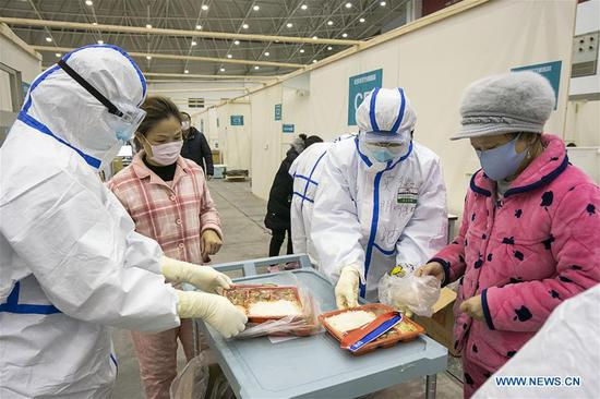 Medical staff distribute food at a temporary hospital converted from