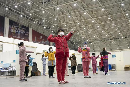 Patients do exercises led by medical staff at a temporary hospital converted from