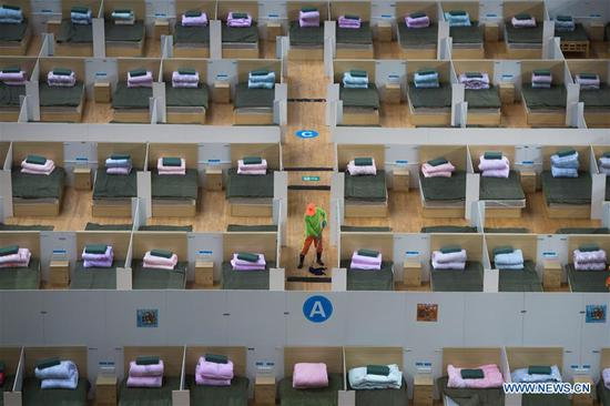 A worker cleans the floor of a temporary hospital converted from Wuhan Sports Center in Wuhan, central China's Hubei Province, Feb. 12, 2020. With the fundamental facilities being set up, the temporary hospital with a total of 1,100 beds is ready to admit patients with mild symptoms caused by the novel coronavirus. (Xinhua/Xiao Yijiu)