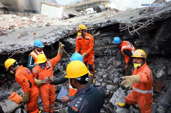 Rescue team members work at the site of a fire incident in Jammu, the winter capital of Indian-controlled Kashmir, Feb. 12, 2020. At least three firefighters were killed and nine others including four civilians injured Wednesday after a building collapsed following a fire incident in Indian-controlled Kashmir, police said. (Xinhua)