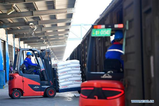 Employees transfer polypropylene material for medical use to a cargo train with forklifts in Lanzhou, northwest China's Gansu Province, Feb. 12, 2020. Lanzhou Petrochemical Company has rushed to work to meet the increasing need of medical material after the novel coronavirus outbreak. (Xinhua/Chen Bin)
