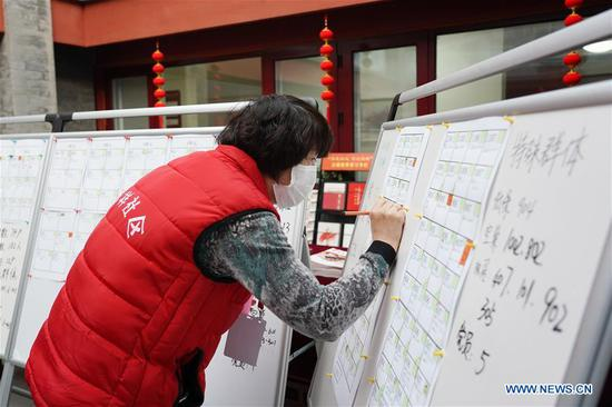 A community staff registers information of residents who have just returned Beijing at Fuxiang community in Dongcheng District in Beijing, capital of China, on Feb. 12, 2020. Work and production has resumed gradually in enterprises, communities and malls, etc. in Beijing since Feb. 10 with comprehensive measures taken to prevent and control the epidemic caused by the novel coronavirus. (Xinhua/Ju Huanzong)