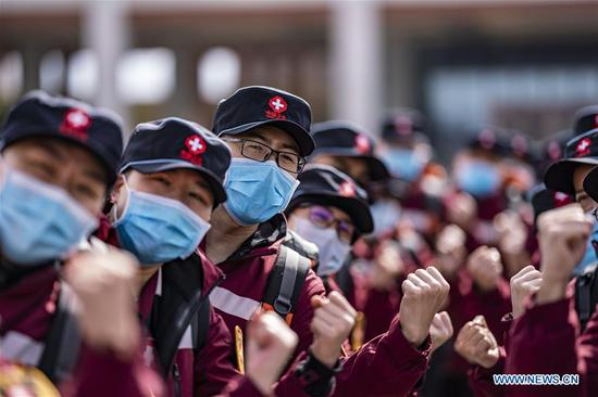 Medical team members gesture to encourage each other before leaving for Xianning City of Hubei Province in Kunming, capital of southwest China's Yunnan Province, Feb. 12, 2020. A medical team comprised of some 350 medical members left for Xianning City of Hubei Province on Wednesday. It's the third medical team sent from Yunnan to aid the novel coronavirus control efforts in Hubei. (Xinhua/Jiang Wenyao)