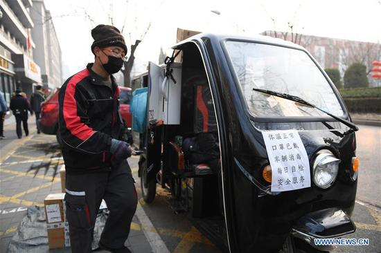 A placard, demonstrating the prevention measures the package delivery company has taken, is seen on the electric tricycle of a deliveryman in Chaoyang District in Beijing, capital of China, on Feb. 12, 2020. Work and production has resumed gradually in enterprises, communities and malls, etc. in Beijing since Feb. 10 with comprehensive measures taken to prevent and control the epidemic caused by the novel coronavirus. (Xinhua/Ju Huanzong)