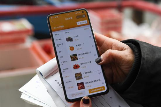 A staff member from a local resident service center displays the WeChat mini-program she uses to provide ordering services for residents in Xicheng District of Beijing, capital of China, Feb. 13, 2020. (Xinhua/Ju Huanzong)