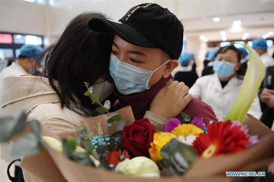 A medical team member (R) of Gansu Provincial Maternity and Child-care Hospital hugs a colleague before leaving for Wuhan in Lanzhou, northwest China's Gansu Province, Feb. 15, 2020. A team comprised of 102 medical workers from Gansu Province left for Wuhan on Saturday to aid the novel coronavirus control efforts there. (Xinhua/Chen Bin)