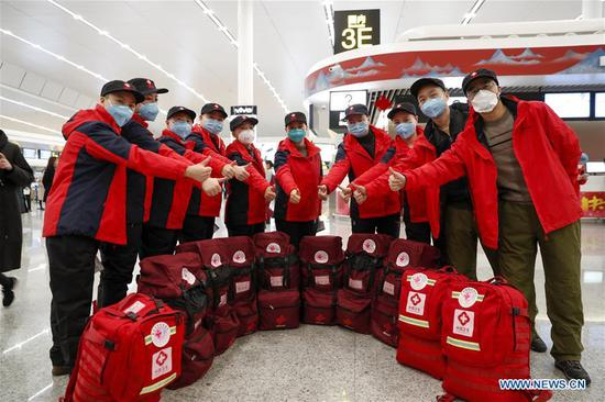 Medical team members of Chongqing Health Center for Woman and Children cheer for each other before leaving for Hubei Province at Chongqing Jiangbei International Airport in southwest China's Chongqing, Feb. 15, 2020. The ninth batch of 100 medical workers from Chongqing left for Hubei Province on Saturday to aid the novel coronavirus control efforts there. (Photo by Huang Wei/Xinhua)