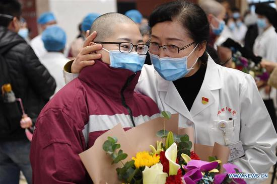 A medical team member (L) of Gansu Provincial Maternity and Child-care Hospital, who has her hair cut to better fit the protective outfits, says goodbye to a colleague before leaving for Wuhan in Lanzhou, northwest China's Gansu Province, Feb. 15, 2020. A team comprised of 102 medical workers from Gansu Province left for Wuhan on Saturday to aid the novel coronavirus control efforts there. (Xinhua/Chen Bin)
