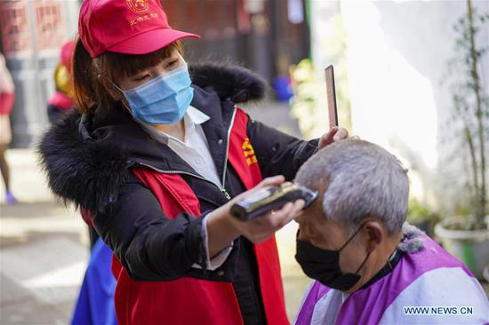 A volunteer barber (L) cuts a man's hair at a community in southwest China's Chongqing Municipality, Feb. 16, 2020. Since the outbreak of the novel coronavirus, most barbershops have been closed. A community in Beibei District of Chongqing organized a team of volunteer barbers to provide free haircuts for its residents. (Xinhua/Liu Chan)