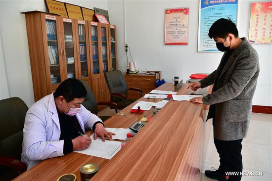A village doctor (L) fills in the medical certificate for a villager planing to work outside at a villagers' committee at Shiqiao Township in Nanyang, central China's Henan Province, Feb. 16, 2020. Nanyang has taken a lot of measures recently to help local workers back to work and promote the export of labor services, diminishing the impact of the novel coronavirus epidemic on the economy. (Xinhua/Feng Dapeng)