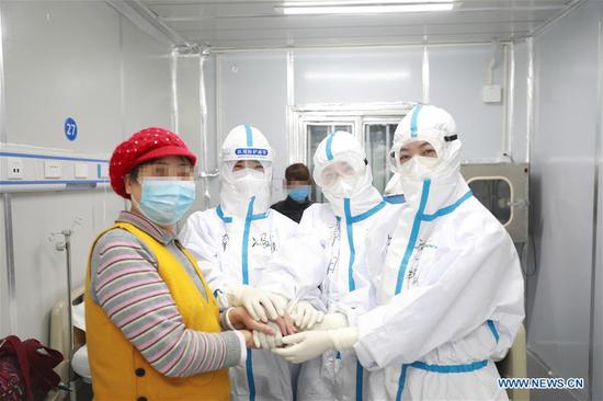 Medical workers comfort for a newly admitted patient at the Leishenshan (Thunder God Mountain) Hospital in Wuhan, capital of central China's Hubei Province, Feb. 16, 2020. The hospital admitted one hundred COVID-19 patients on Sunday. (Photo by Gao Xiang/Xinhua)