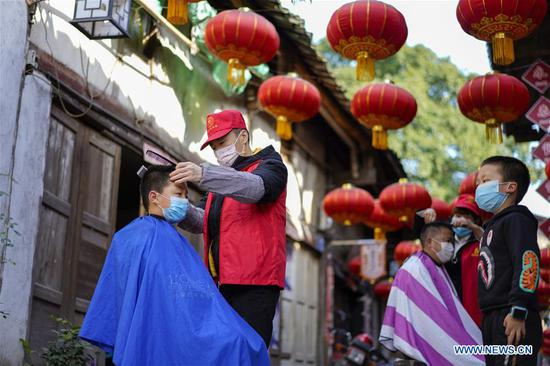 A volunteer barber cuts a boy's hair at a community in southwest China's Chongqing Municipality, Feb. 16, 2020. Since the outbreak of the novel coronavirus, most barbershops have been closed. A community in Beibei District of Chongqing organized a team of volunteer barbers to provide free haircuts for its residents. (Xinhua/Liu Chan)