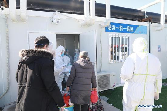 Patients walk into a ward at the Leishenshan (Thunder God Mountain) Hospital in Wuhan, capital of central China's Hubei Province, Feb. 16, 2020. The hospital admitted one hundred COVID-19 patients on Sunday. (Photo by Gao Xiang/Xinhua)