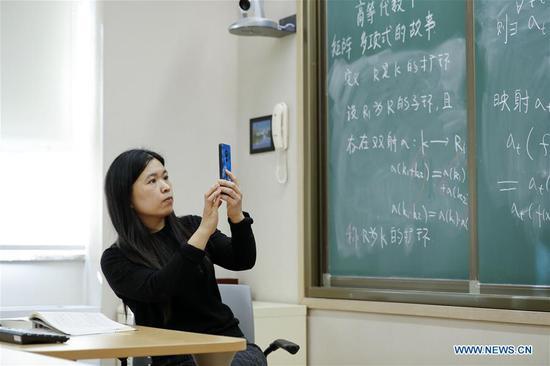 Zhao Yufeng, a teacher of Peking University, uses online educational system