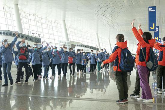Medical staffers from east China's Shandong Province (L) wave to their peers from east China's Jiangsu Province at the Wuhan Tianhe International Airport, in Wuhan, central China's Hubei Province, March 17, 2020. Some medical assistance teams started leaving Hubei Province on Tuesday as the epidemic outbreak in the hard-hit province has been subdued. (Xinhua/Xiong Qi)