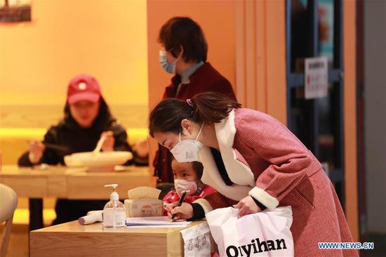 A customer registers her information before entering a restaurant in Lanzhou, northwest China's Gansu Province, March 18, 2020. Local restaurants have restored dine-in service with strict measures taken to fight against the COVID-19 in recent days. (Xinhua/Du Zheyu)