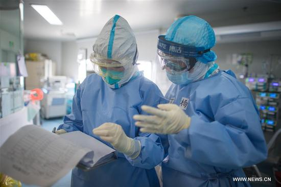 Members of medical assistance team from Zhejiang are busy at the ICU (intensive care unit) of Wuhan pulmonary hospital in Wuhan, central China's Hubei Province, March 19, 2020. The medical assistance team from Sir Run Run Shaw Hospital in east China's Zhejiang Province finished its mission in the ICU of Wuhan Xiehe Hospital amid the fight against the novel coronavirus outbreak on Thursday. At the same day, the team moved to Wuhan pulmonary hospital and continued to work alongside with the hospital's staff and medical assistant team from north China's Inner Mongolia Autonomous Region to treat critically ill patients of COVID-19 here. (Xinhua/Xiao Yijiu)