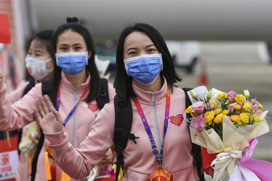 Medics supporting virus-hit Hubei Province pose for photos after disembarking from the plane at Nanning Wuxu International Airport in Nanning, south China's Guangxi Zhuang Autonomous Region, March 20, 2020. The second batch of the medical assistance team from Guangxi, which consist of 136 members, had left Hubei Province, as the epidemic outbreak in the hard-hit province has been subdued. (Xinhua/Cao Yiming)