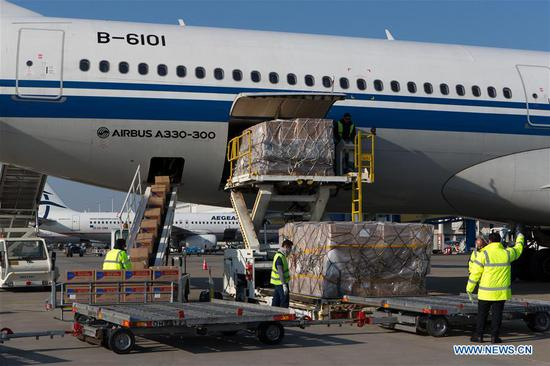 Airport staff unload boxes of face masks and medical supplies from an airplane of Air China, in Athens, Greece, on March 21, 2020. Approximately eight tons of medical supplies provided by the Chinese government to Greece after Athens' urgent request arrived on Saturday morning at Athens international airport on an Air China flight.The aid consists of 550,000 masks and sets of protective gear, according to a release issued by the Chinese embassy in Greece. (Xinhua/Marios Lolos)