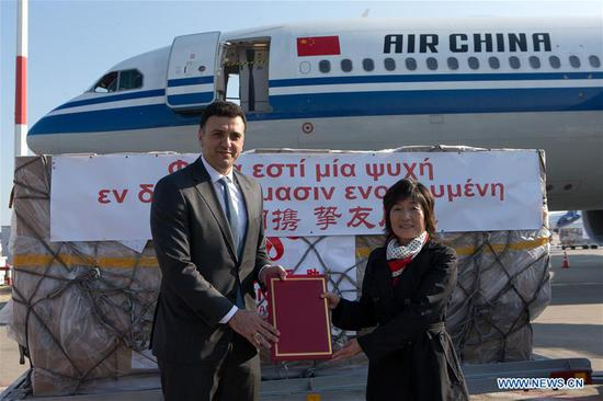 Chinese Ambassador to Greece Zhang Qiyue (R) and Greek Health Minister Vasilis Kikilias attend the handover ceremony of medical supplies in Athens, Greece, on March 21, 2020. Approximately eight tons of medical supplies provided by the Chinese government to Greece after Athens' urgent request arrived on Saturday morning at Athens international airport on an Air China flight.The aid consists of 550,000 masks and sets of protective gear, according to a release issued by the Chinese embassy in Greece. (Xinhua/Marios Lolos)