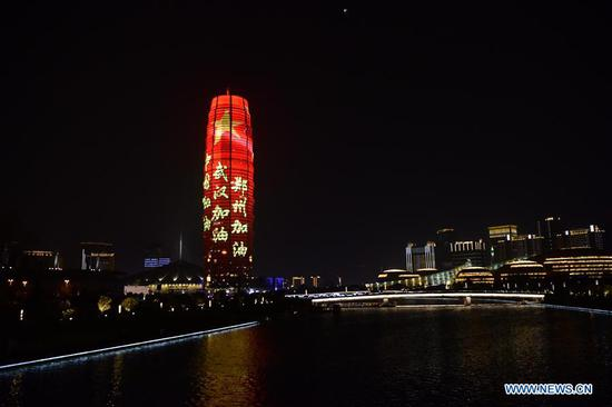 A building is illuminated with slogans honoring people fighting against COVID-19, in Zhengzhou, central China's Henan Province, March 21, 2020. (Xinhua/Zhu Xiang)