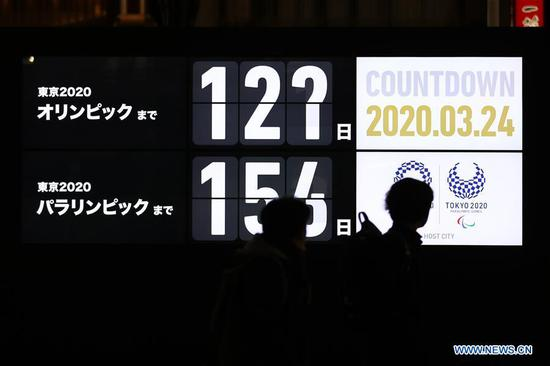 A pedestrian walks near a Tokyo 2020 Olympic Games countdown display in Shimbashi district of Tokyo, Japan, March 24, 2020. Japanese Prime Minister Shinzo Abe announced on Tuesday that Japan and the International Olympic Committee (IOC) have agreed to postpone the Tokyo Olympic and Paralympic Games by one year. (Xinhua/Du Xiaoyi)