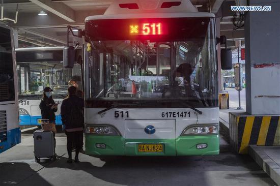 People wait to get on a bus in Wuhan, central China's Hubei Province, March 25, 2020. Wuhan, the once hardest-hit city in central China's Hubei Province during the COVID-19 outbreak, resumed a total of 117 bus routes starting Wednesday, around 30 percent of the city's total bus transport capacity, the municipal transport bureau said. According to a spokesperson of the bureau, passengers must wear masks, register with their names and scan a QR code, and take a temperature check before taking buses and subways. (Xinhua/Cai Yang)