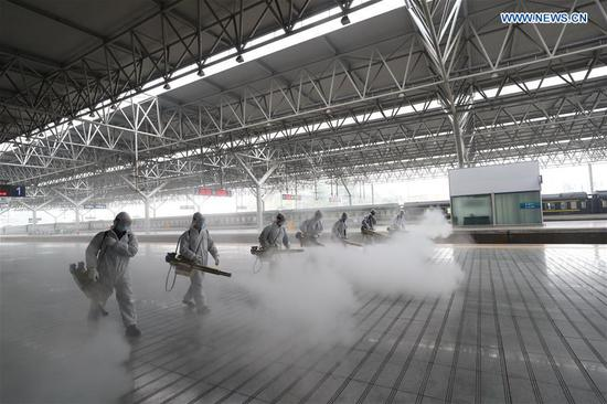 Firefighters conduct disinfection on the platform at Yichang East Railway Station in Yichang, central China's Hubei Province, March 24, 2020. About 50 firefighters conducted a comprehensive disinfection at the railway station on Tuesday. (Photo by Wang Shen/Xinhua)