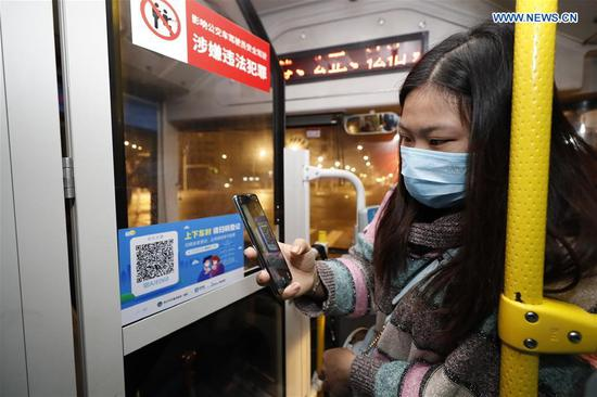 A passenger scans a QR code for registration on a bus in Wuhan, central China's Hubei Province, March 25, 2020. Wuhan, the once hardest-hit city in central China's Hubei Province during the COVID-19 outbreak, resumed a total of 117 bus routes starting Wednesday, around 30 percent of the city's total bus transport capacity, the municipal transport bureau said. According to a spokesperson of the bureau, passengers must wear masks, register with their names and scan a QR code, and take a temperature check before taking buses and subways. (Xinhua/Shen Bohan)