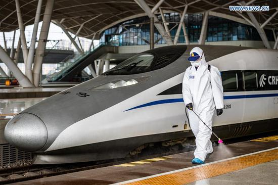 A firefighter conducts disinfection on the platform of Wuhan Railway Station in Wuhan, central China's Hubei Province, March 24, 2020. Over 70 firefighters conducted a comprehensive disinfection at the railway station on Tuesday. (Photo by He Hanqiu/Xinhua)