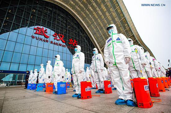 Firefighters gather to prepare for disinfection works at the Wuhan Railway Station in Wuhan, central China's Hubei Province, March 24, 2020. Over 70 firefighters conducted a comprehensive disinfection at the railway station on Tuesday. (Photo by He Hanqiu/Xinhua)
