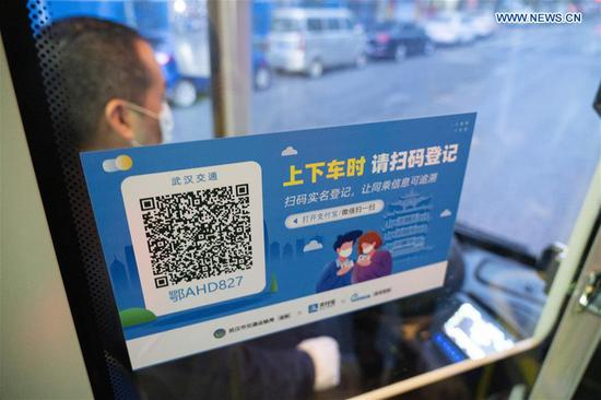 Photo taken on March 25, 2020 shows a QR code for registration in a bus in Wuhan, central China's Hubei Province. Wuhan, the once hardest-hit city in central China's Hubei Province during the COVID-19 outbreak, resumed a total of 117 bus routes starting Wednesday, around 30 percent of the city's total bus transport capacity, the municipal transport bureau said. According to a spokesperson of the bureau, passengers must wear masks, register with their names and scan a QR code, and take a temperature check before taking buses and subways. (Xinhua/Cai Yang)