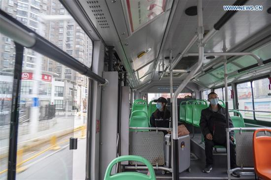 People take a bus in Wuhan, central China's Hubei Province, March 25, 2020. Wuhan, the once hardest-hit city in central China's Hubei Province during the COVID-19 outbreak, resumed a total of 117 bus routes starting Wednesday, around 30 percent of the city's total bus transport capacity, the municipal transport bureau said. According to a spokesperson of the bureau, passengers must wear masks, register with their names and scan a QR code, and take a temperature check before taking buses and subways. (Xinhua/Cai Yang)