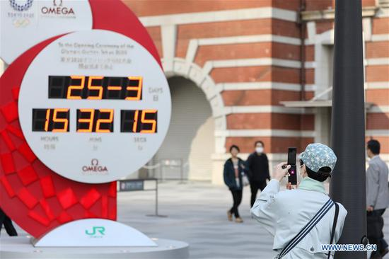 A pedestrain takes photos of a countdown clock no longer showing the days left until the opening ceremony of Tokyo Olympic Games in Tokyo, Japan on March 25, 2020. Organizers of the Tokyo Olympic Games (Tokyo 2020) will set up task force to resolve the issues arising after the postponement of the Olympic and Paralympic Games. (Xinhua/Du Xiaoyi)