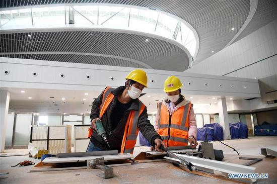 Staff members work at the terminal building of Jiaodong International Airport in Qingdao, east China's Shandong Province, March 25, 2020. The construction work of the airport was fully resumed recently. (Xinhua/Li Ziheng)