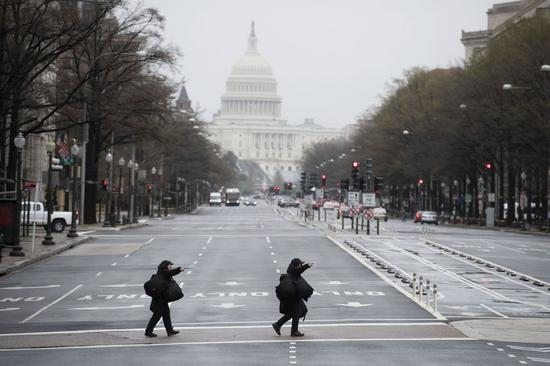 Photo taken on March 23, 2020 shows two pedestrians walking on a nearly empty street in Washington D.C., the United States. (Xinhua/Liu Jie)