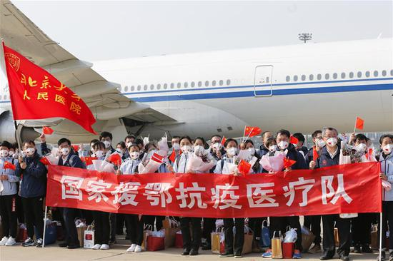 Members of the national medical team pose for a photo after arriving at Beijing Capital International Airport in Beijing, capital of China, April 6, 2020. A national medical team of 557 medical workers returned to Beijing on Monday after aiding Hubei Province in the fight against the COVID-19. (Xinhua/Zhang Yuwei)