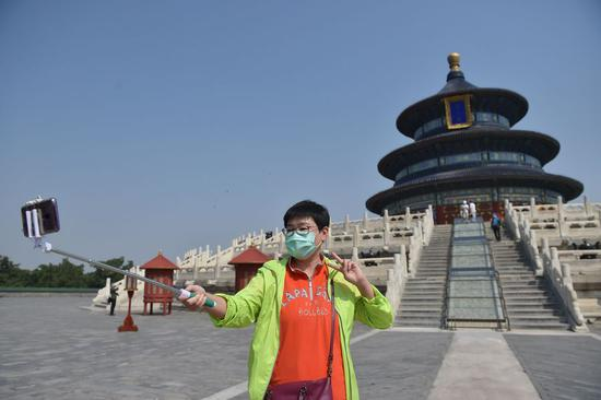 A tourist poses for a selfie in front of the Hall of Prayer for Good Harvests at the Temple of Heaven in Beijing, April 29, 2020. (Xinhua/Peng Ziyang)